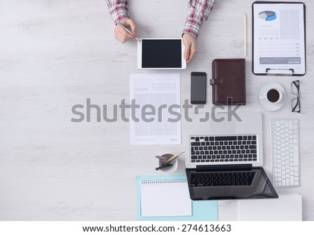 Businessman working at office desk and using a digital touch screen tablet hands detail, computer and objects on the right, top view - stock photo