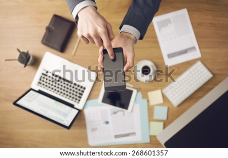 Businessman working at office desk hands top view with laptop and financial reports: he is using a mobile touch screen smart phone - stock photo