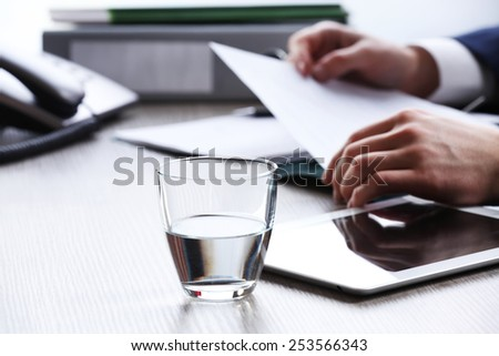 Businessman working at table in office on white blurred background - stock photo