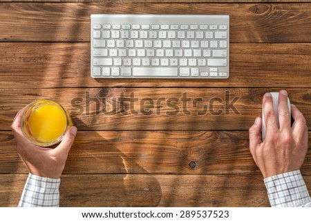 Businessman working at vintage crafted wooden desk. From above prospective on clean working place with keyboard mouse glass orange juice hands of person working - stock photo