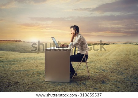 Businessman working in a field - stock photo