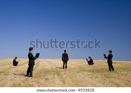 businessman working in a field making a teamwork with the nature - stock photo