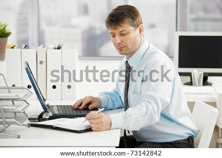Businessman working in office, searching in personal organizer.? - stock photo