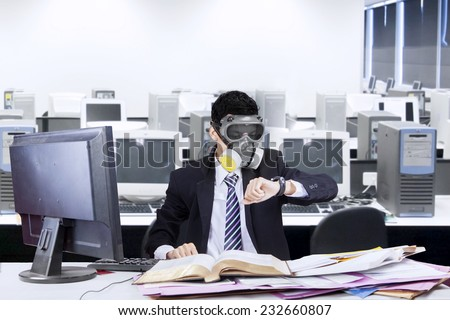 Businessman working in office with a gas mask and looking at his watch - stock photo