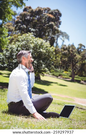 Businessman working in the park on a sunny day - stock photo