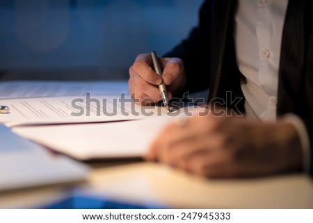 Businessman working late signing a document or contract in a dark office with a fountain pen by the light of a lamp, close up view of his hands. - stock photo