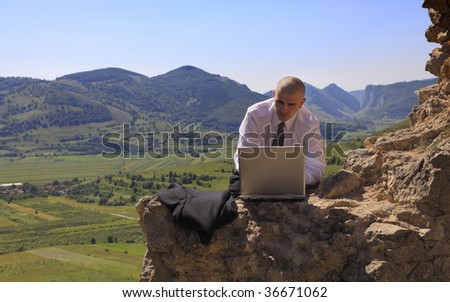 Businessman working on a computer outdoors. - stock photo