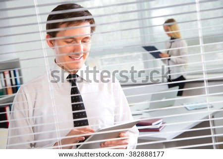 Businessman working on a tablet computer at the office blinds. - stock photo