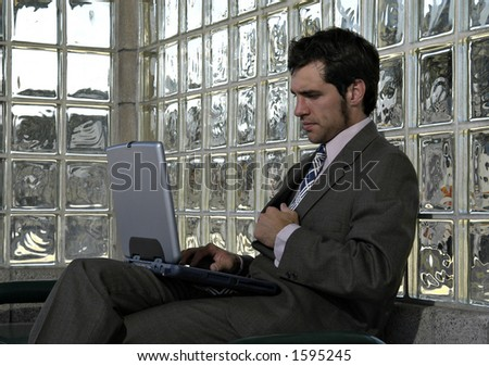 businessman working on his laptop in an airport, train, or bus station - stock photo