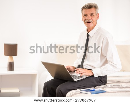 Businessman working on laptop and looking at camera while sitting on bed at the hotel room. - stock photo