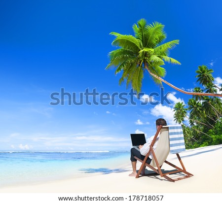 Businessman Working on laptop at Tropical Beach - stock photo
