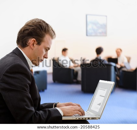 Businessman working on laptop computer at office lobby. - stock photo