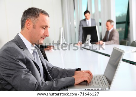 Businessman working on laptop computer in office - stock photo