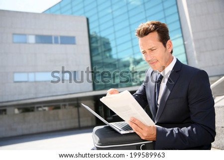 Businessman working on laptop computer outside the office  - stock photo