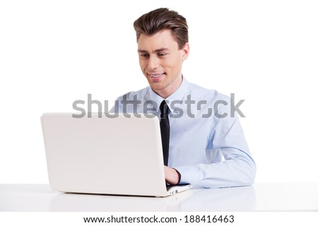 Businessman working on laptop. Handsome young man in shirt and tie sitting at the table and working on laptop while isolated on white   - stock photo