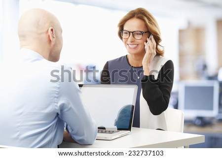 Businessman working on laptop while business woman talking on mobile phone. Business meeting.  - stock photo
