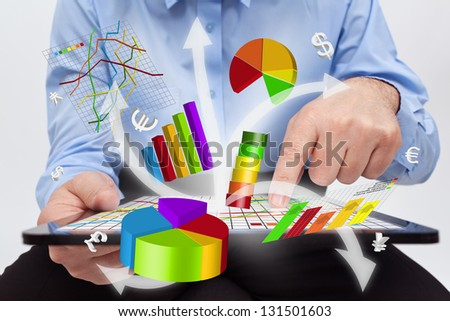 Businessman working on tablet computer - producing charts and reports - stock photo