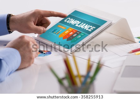 Businessman working on tablet with COMPLIANCE on a screen - stock photo