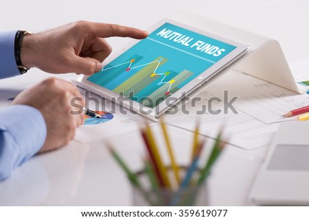 Businessman working on tablet with MUTUAL FUNDS on a screen - stock photo