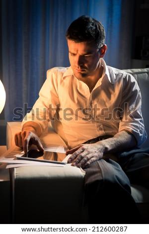 Businessman working overtime late at night in the living room, with tablet and paperwork. - stock photo
