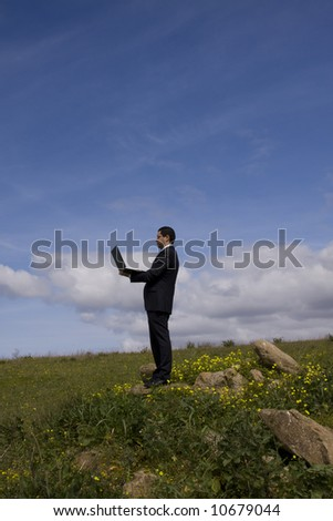 businessman working with a laptop in a field - stock photo