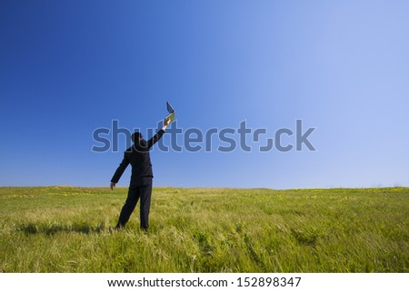 Businessman working with a laptop outdoor on a field - stock photo