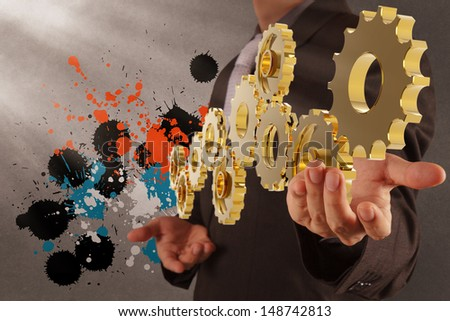 businessman working with gear and splash colors  as concept - stock photo