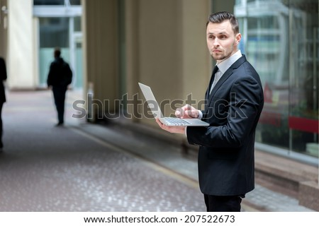 Businessman working with laptop. Businessman talking with a newspaper in his hands forward within an office building. Young business in formal dress - stock photo