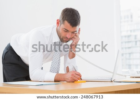 Businessman write informations given on the phone at his desk - stock photo