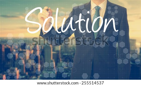businessman write on transparent board Solution with sunset over the city in the background, the sun's rays falling into lens are symbolizing the good attitude - stock photo