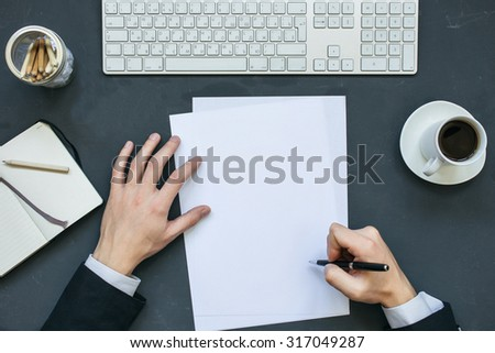 Businessman writing a letter at office working table with notepad, computer and cup of coffee. Top view. - stock photo