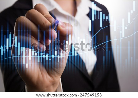 Businessman writing analyze graph for trade stock market on the screen. - stock photo
