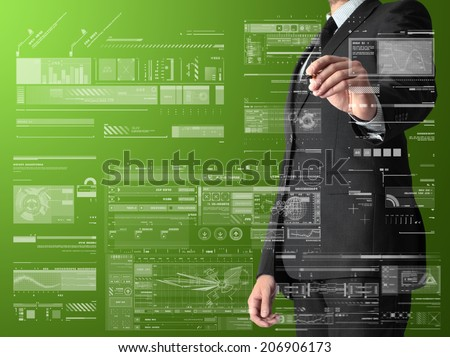 businessman writing and drawing graphs and diagrams on green background - stock photo