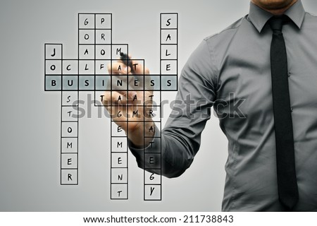 businessman writing business concept by crossword - stock photo