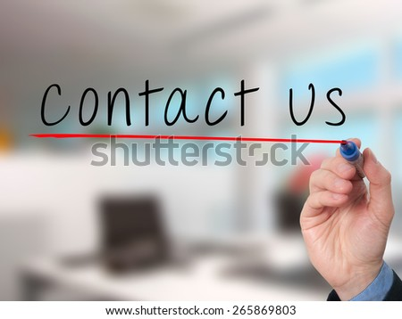 Businessman writing contact us against office background. Stock Image - stock photo