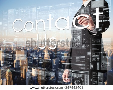 businessman writing Contact Us on transparent board with city in background  - stock photo