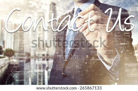 Businessman writing Contact Us on virtual screen behind the back of the businessman one can see the city behind the window - stock photo
