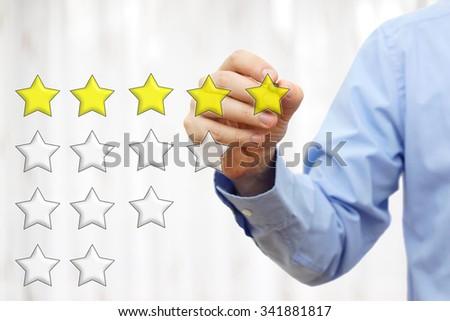 businessman writing  five star rating - stock photo