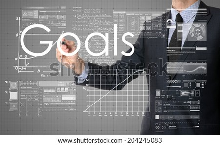 businessman writing Goals and drawing some sketches - stock photo