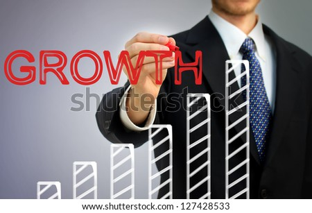 Businessman writing growth over a rising bar graph - stock photo