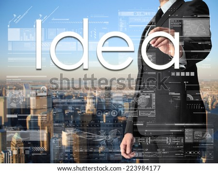 businessman writing Idea on transparent board with city in background - stock photo