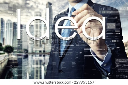 Businessman writing Idea on virtual screen behind the back of the businessman one can see the city behind the window - stock photo