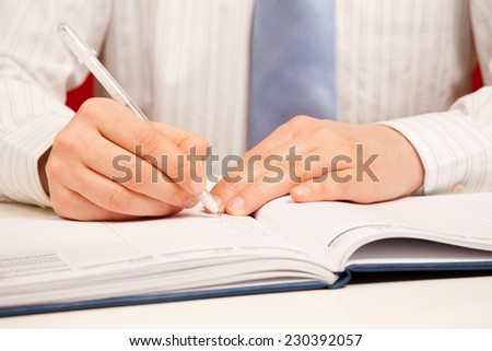 Businessman writing in his planer - stock photo