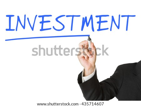 """Businessman writing """"investment"""" on whiteboard with marker - stock photo"""