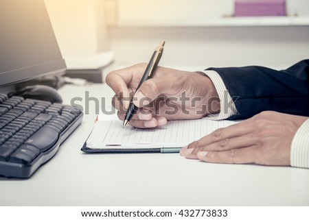 Businessman writing on notebook with pen in the office in vintage color tone - stock photo