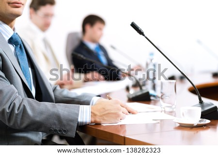 Businessman writing on paper notes, to communicate with colleagues in the background - stock photo