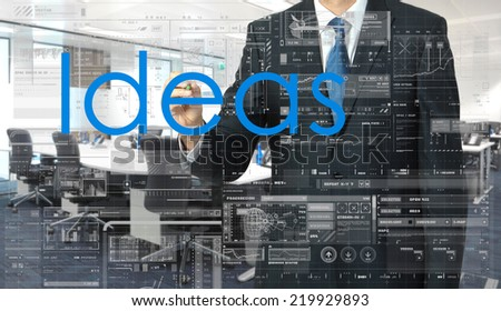 businessman writing on transparent board Ideas with office in background - stock photo