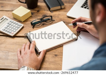 Businessman writing or drawing a note in a blank notebook  - stock photo