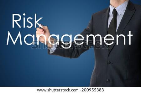 businessman writing risk management on blue background - stock photo
