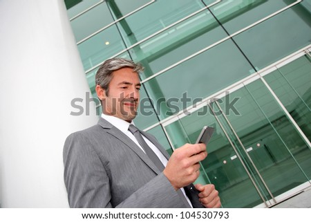 Businessman writing short message on mobile phone - stock photo